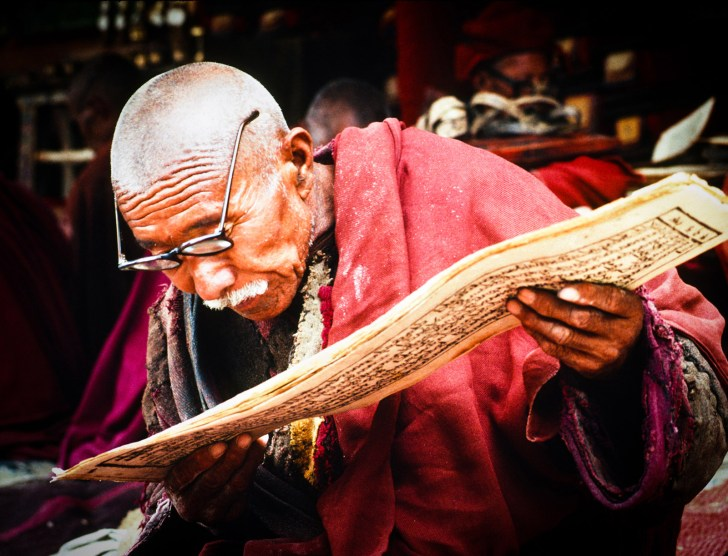 Monk recites the fundamental texts of Buddhism, the Kanjur, during an eight day ceremony, Lingshed monastery. Ladakh. India. 1993.