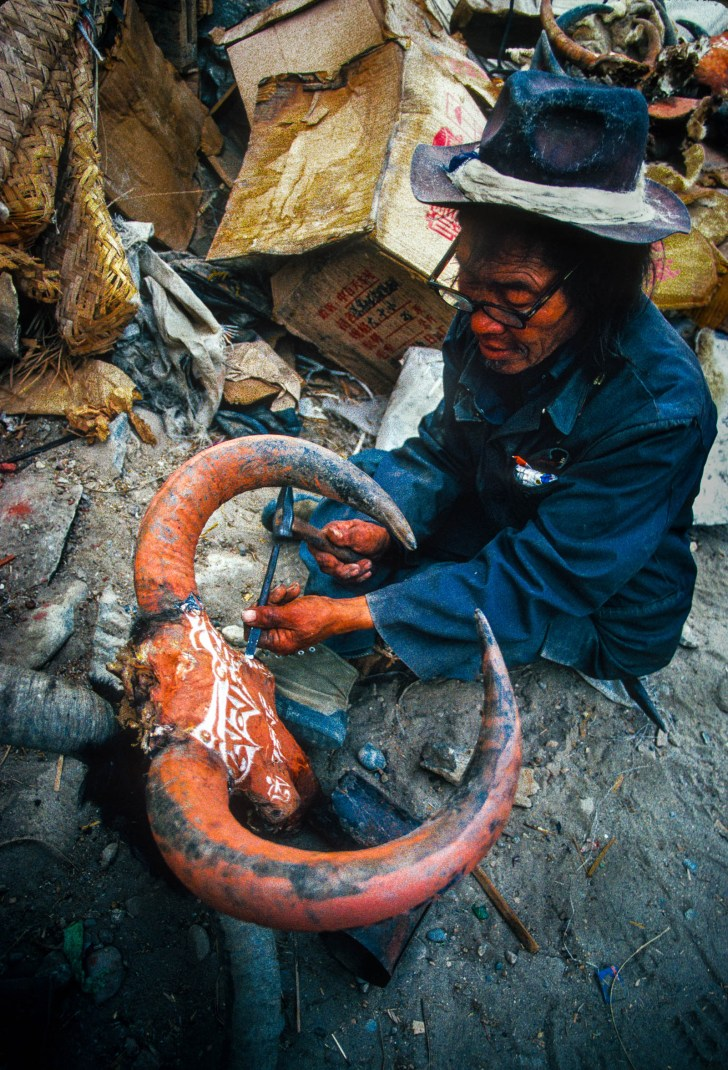 A layman carves Tibetan Buddhist prayers on yak skull in Burang, village near Nepal/India border, Ngari district, Tibet 1987