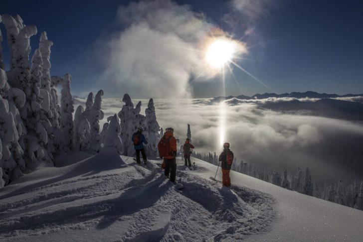 heli skiers above to drop in on their next run of powder