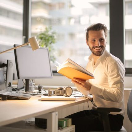Man with handbook in office