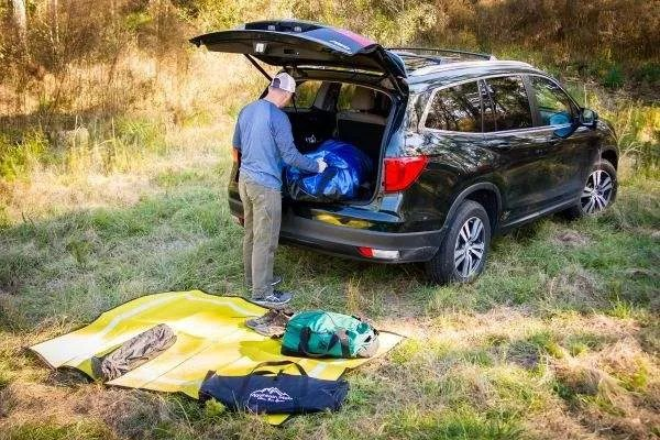 man unpacking camping gear from trunk onto outdoor camping ground mat