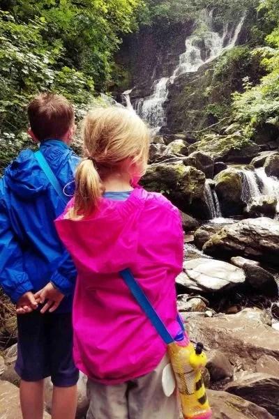 boy and girl looking at waterfall