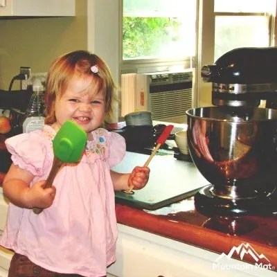 toddler holding a spatula and standing next to mixer