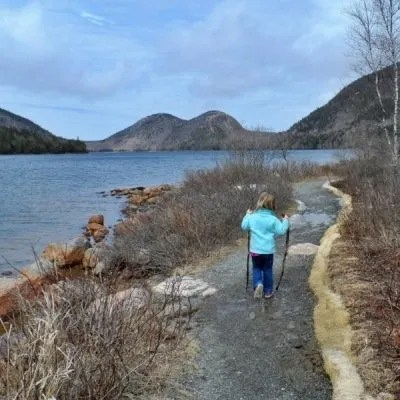 young girl hiking on path near lake in Maine