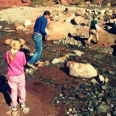 a man and children building a rock bridge across a small stream