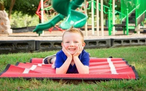 little boy lying on outdoor camping mat