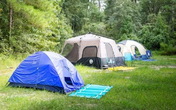 campsite with three tents with camping mats