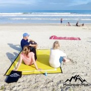 family sitting on yellow mountain mat beach mat