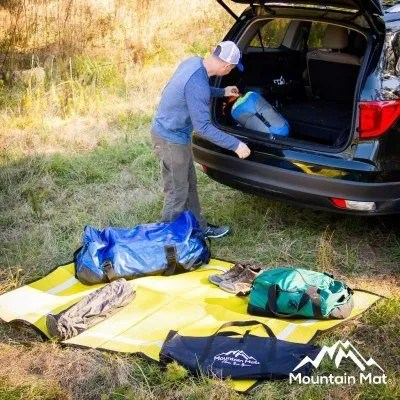 man unloading camping gear from back of car onto camping mat