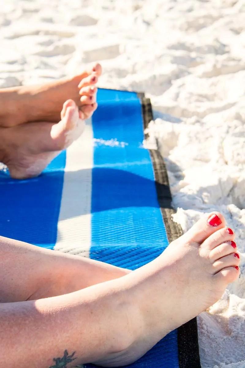 feet on blue beach blanket by Mountain Mat