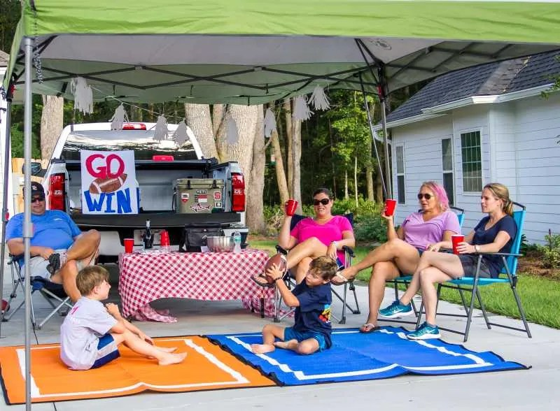Tailgate Party with eco-friendly recycled plastic tailgate rugs in team colors orange and blue size 5x7