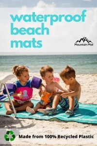 3 little kids sitting on a beach mat
