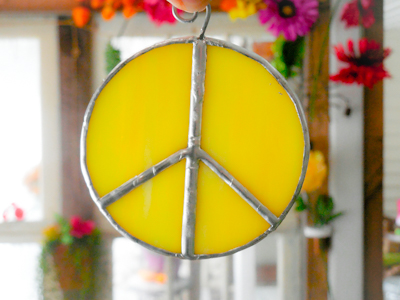 Yellow stained glass peace sign suncatcher with flowers in the background