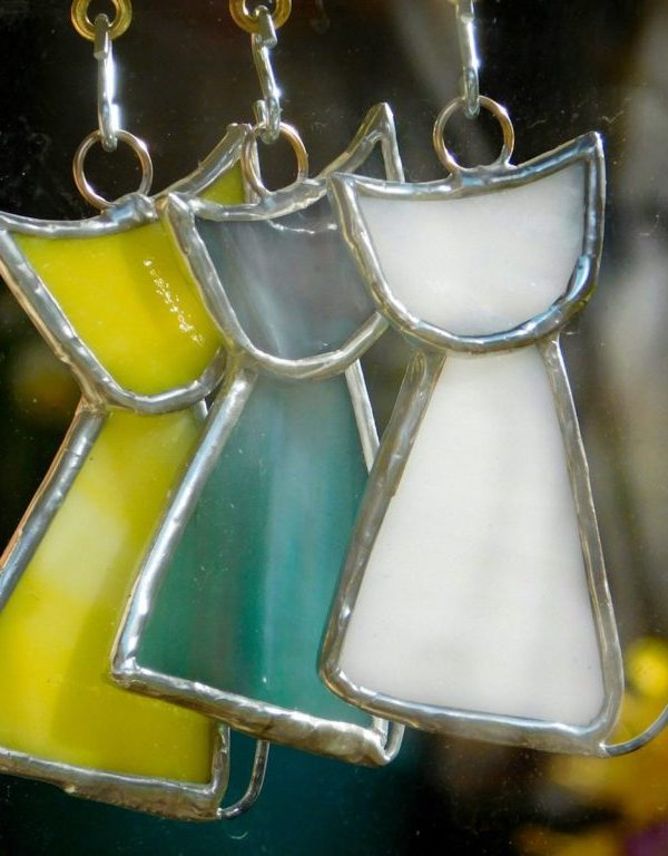 Stained glass scrappy cats hanging in a window.
