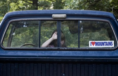 Chad A. Stevens / milesfrommaybe Productions The daughter of a resident of Rock Creek, W. Va., waits in the vehicle while her guardian inspects a reclaimed mountaintop removal site in near Kayford Mountain in West Virginia.