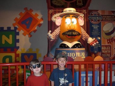 My boys hang out with Mr. Potato Head while we wait to test our skills on Toy Story's Midway Mania.