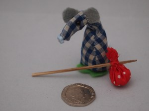 Microvaark shows off his spotty hanky on a stick, with a coin for scale