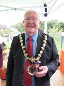 Ratvaark, in his waistcoat and cape, sits in the hand of Salford's ceremonial mayor, who is wearing a gold chain.