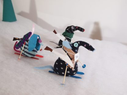 Winston, Bernard and Ofelia are skiing across a snowy landscape, carrying rifles