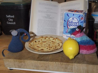 Ernest and Ratvaark admire their pancake, with a lemon and bag of sugar