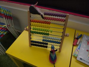 Fury sits on top of an abacus. The lines of beads that are the colour of Ratvaark's stripes are pushed across