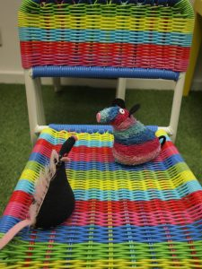 Fury and Ratvaark sit on a striped chair. Ratvaark sits on the stripes that match his fur
