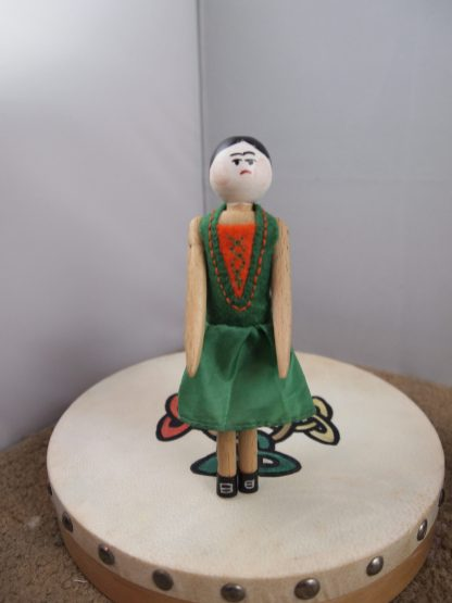 Peggy is standing on a stage made from a real Irish drum, wearing a green and orange dress and black silver buckled shoes