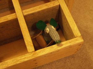 A vaark is visible hiding in one of the bottle spaces in a wooden milk bottle crate