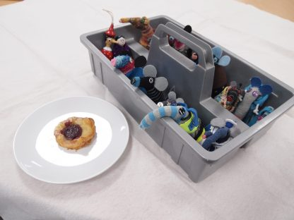 The whole clan peer out of their box at a danish pastry on a plate