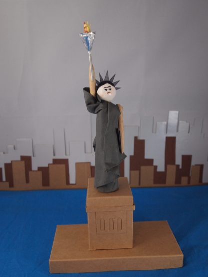 A close up of the Statue of Liberty, who is played by Peggy in a robe and headress