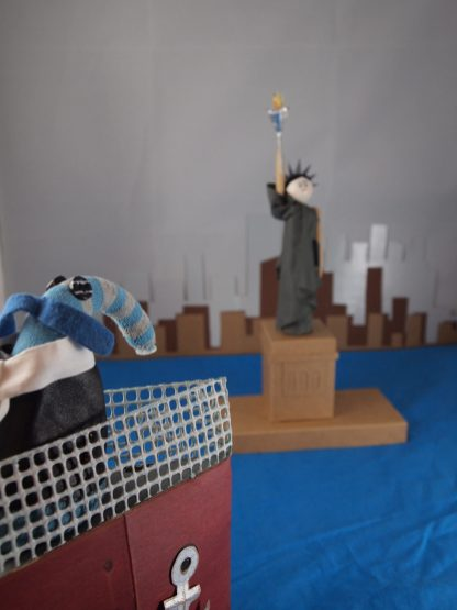 Arnold stands on the prow of the ship, looking at the Statue of Liberty and the city skyline