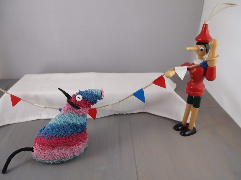 Ratvaark and Gino put up red white and blue bunting, over a long table with a white cloth on it.