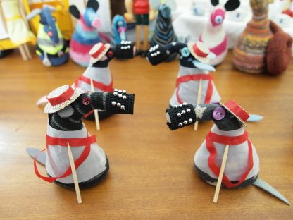 Four vaarks are dressed in white smocks with red sashes and straw hats with bells on their snozzles