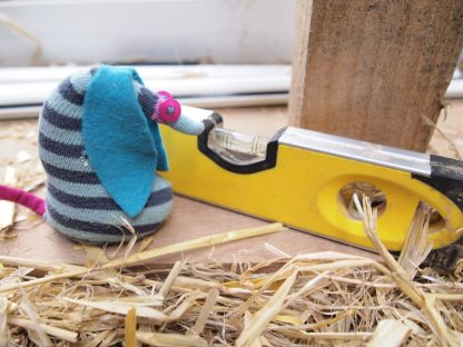 Ofelia looks at a spirit level on a straw bale