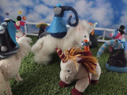 Arnold watches as horses (played by toy unicorns) circle round with vaark jockeys on their backs