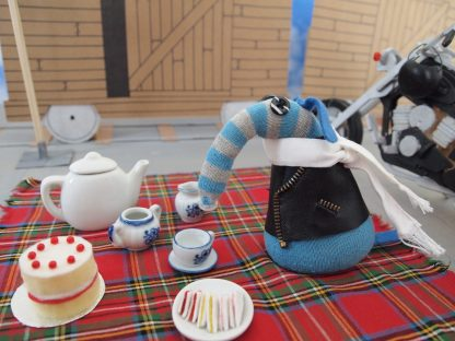 Arnold has a picnic with a full tea set, a plate of sandwiches and a sponge cake on a tartan blanket.