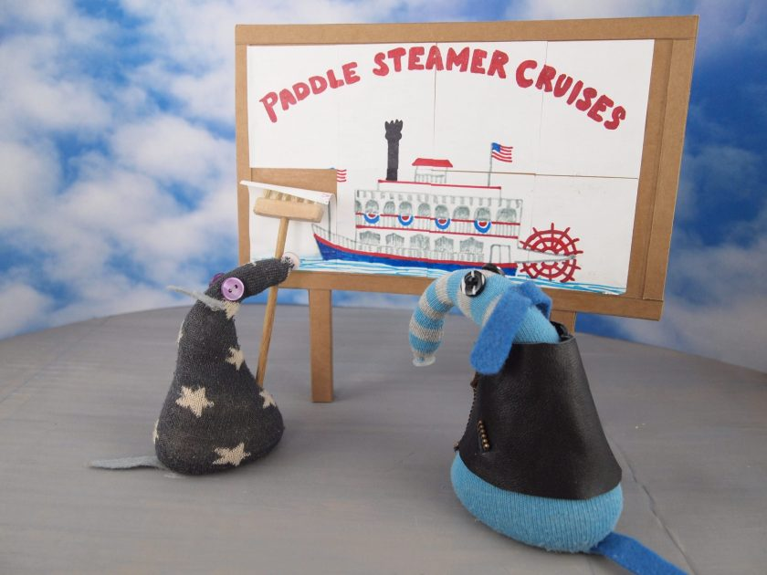 Arnold looks at a billboard where a vaark who looks like Vincent is pasting up a poster advertising paddle steamer cruises