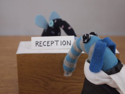Arnold is at a reception desk, talking to the vaark on duty