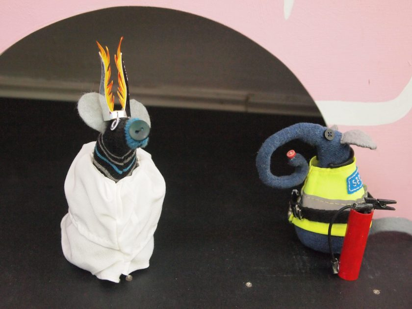 Ernest is looking at Hypnovaark who is dressed in a white robe with a flaming headress, like Arthur Brown