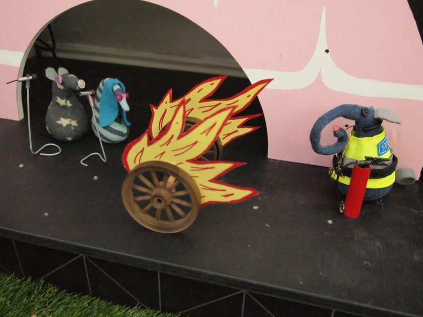 A pair of wheels, trailing flames, roll across the stage
