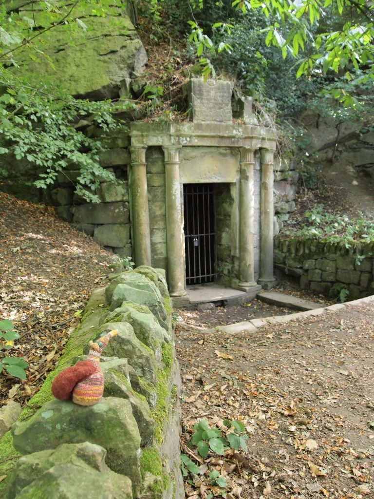 Esther looks at an ornate stone doorway in the side of a hill