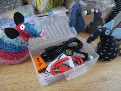 Ratvaark and Winston look at a plastic box with more leads and USB devices in it