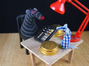 Bernard counts chocolate coins at his desk as Microvaark watches