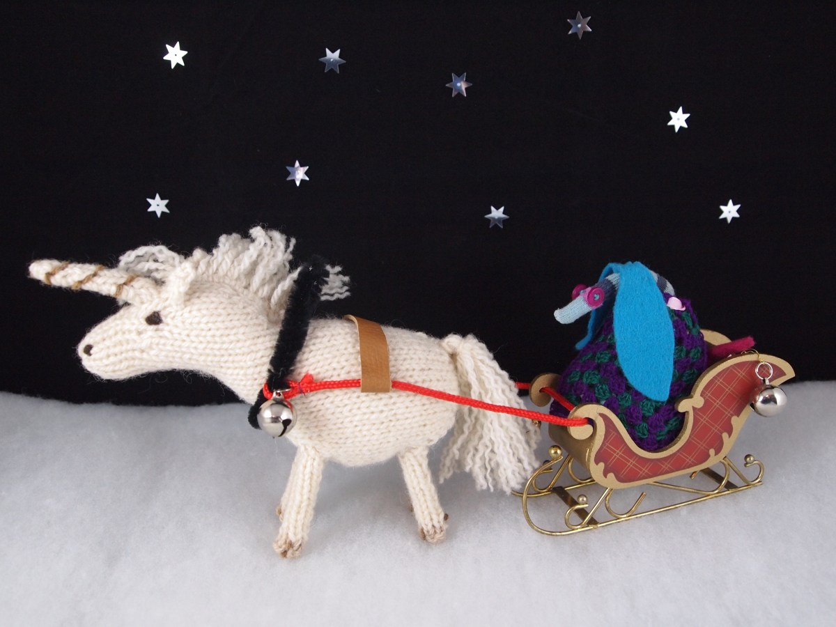 Ofelia rides in a sleigh, pulled by a knitted unicorn.
