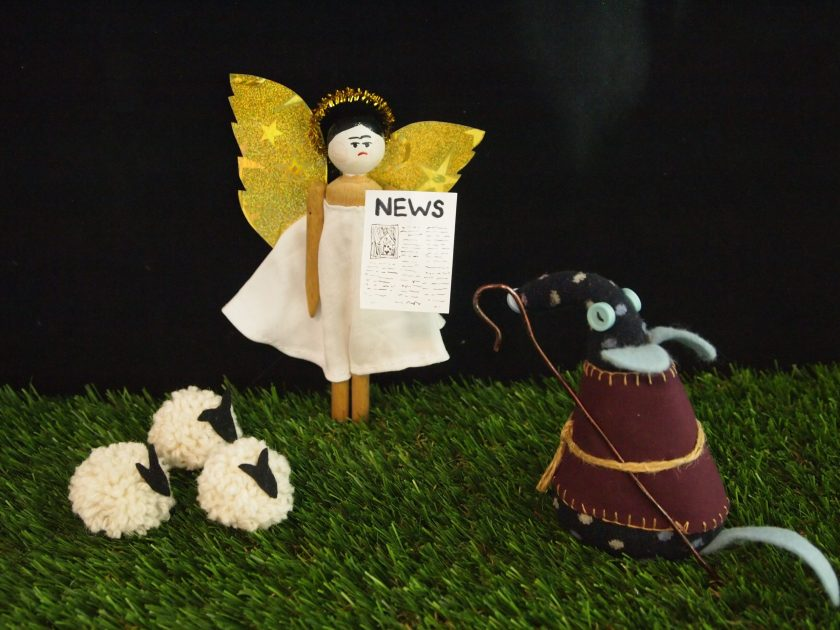 Peggy dressed as an angel, presents news to Winston dressed as a shepherd.