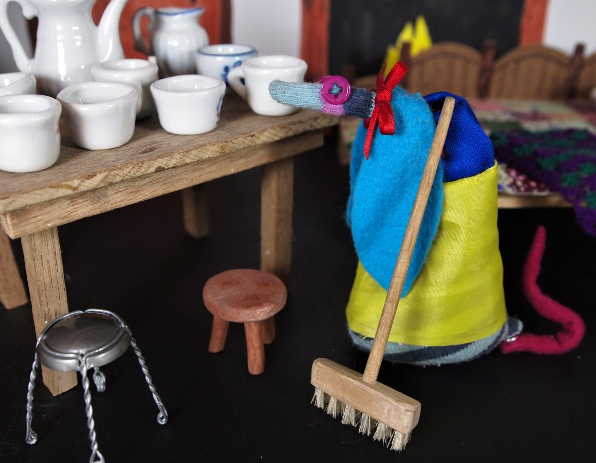 Snow White tidies up and sweeps with a broom