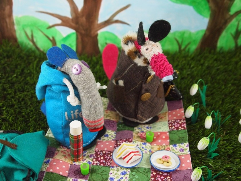 Dim and Matilda sit on a patchwork rug, with a tartan thermos, a plate of sandwiches and a plate of doughuts