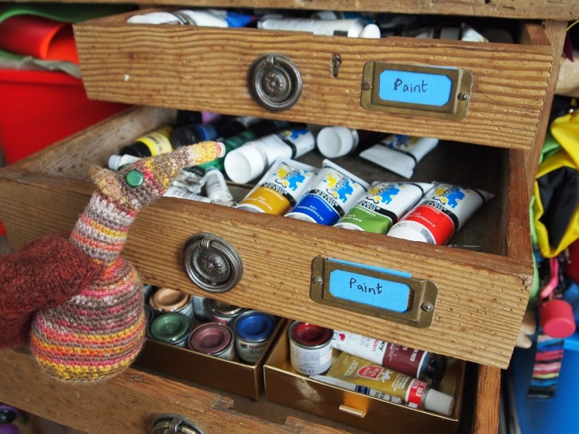 Esther looks in a drawer of tubes of paint