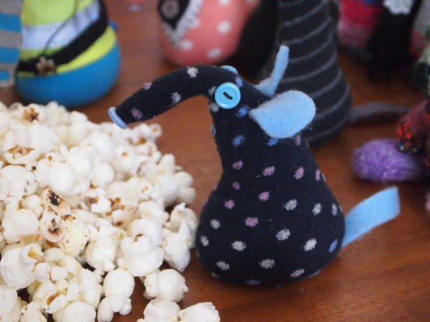 winston, missing his hat, looks into the pile of popcorn