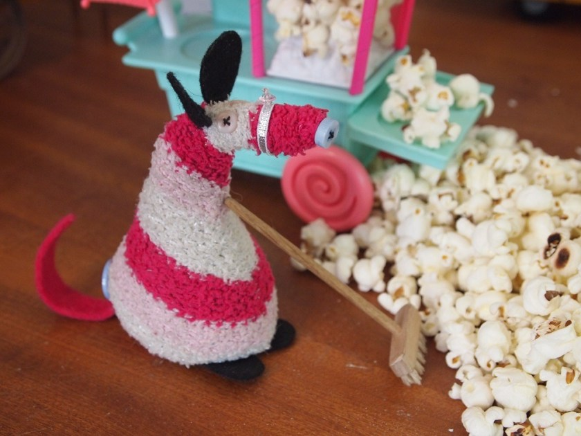 matilda sweeps up the popcorn with a broom